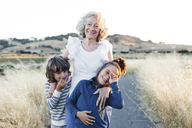 Portrait of happy grandmother with grandsons on country road - CAVF25507