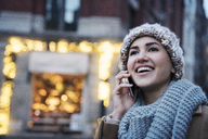 Close-up of happy woman talking on mobile phone in city - CAVF25651