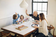 Family enjoying while eating pizza at dining table in home - CAVF25660
