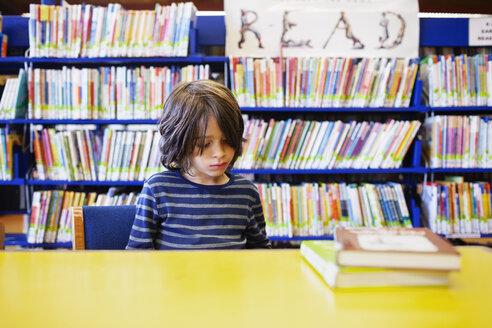Cute boy sitting against bookshelf in library - CAVF25735