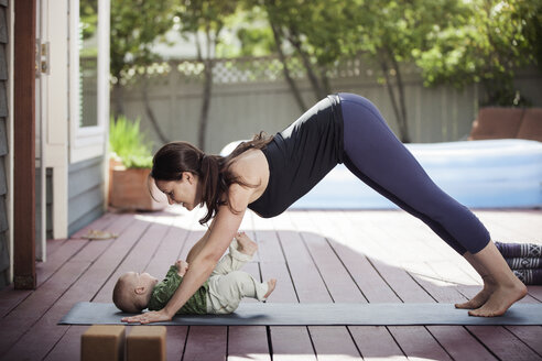 Side view of woman practicing downward facing dog position while looking at baby in backyard - CAVF25795