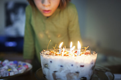 Midsection of boy with birthday cake at table - CAVF25846