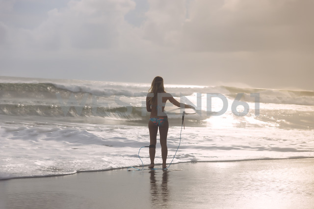Indonesia, Bali, Young woman with surfboard - KNTF01103
