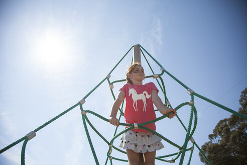 Low angle view of girl looking away while playing on jungle gym - CAVF25924