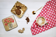 Overhead view of cookies in container by latte cup on napkin at table - CAVF26014