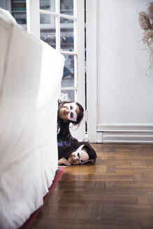 Portrait of sisters wearing eye masks peeking by sofa at home - CAVF26068