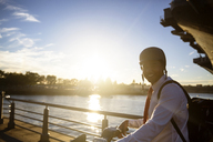 Portrait of businessman with bicycle standing against river during sunset - CAVF26182