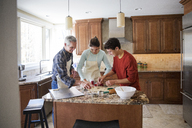 Happy family preparing gingerbread cookies in kitchen at home - CAVF26185