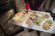 Senior man holding gingerbread cookies in baking sheet at home - CAVF26188