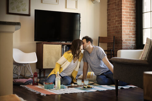 Couple kissing while sitting on carpet at home - CAVF26311