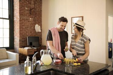 Happy couple preparing food in kitchen - CAVF26329