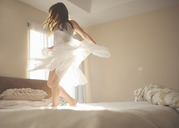 Playful girl dancing on bed at home - CAVF26401