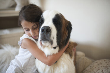 Girl embracing Saint Bernard while sitting on bed at home - CAVF26422