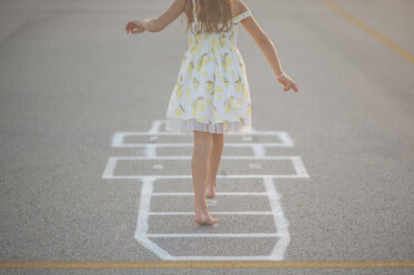 Low section of girl playing hopscotch on footpath - CAVF26428