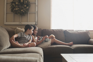 Siblings playing on baby boy while sitting on sofa at home - CAVF26449
