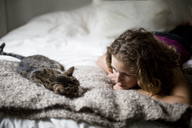 Woman looking at cat while lying on bed at home - CAVF26503