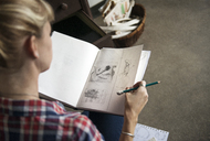 Female artist looking at sketches in book while sitting at home - CAVF26656