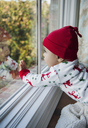 Baby boy looking through window at home - CAVF26659