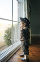 Boy wearing hat while looking through window at home - CAVF26662