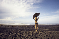 Rear view of woman carrying surfboard while walking at beach against sky - CAVF26691