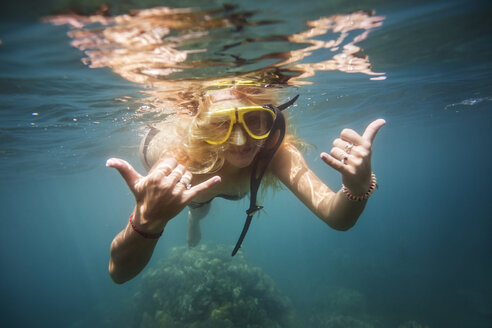 Woman gesturing while swimming in sea - CAVF26778