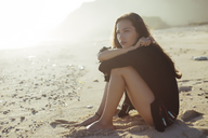 Thoughtful woman hugging knees while sitting at beach during sunny day - CAVF26862