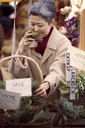 Happy mature woman smelling thyme at farmer's market stall - CAVF26892