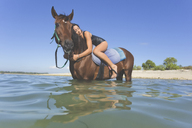 Indonesia, Bali, Woman lying on horse, in water - KNTF01106