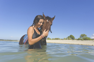 Indonesia, Bali, Woman with horse in the water - KNTF01109