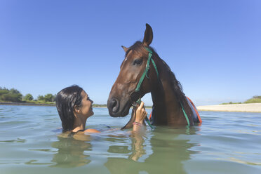 Indonesia, Bali, Woman with horse in the water - KNTF01112