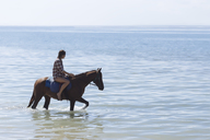 Indonesia, Bali, Woman riding a horse at beach - KNTF01115