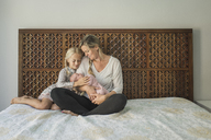 Mother and daughter looking at newborn baby while sitting on bed - CAVF26963