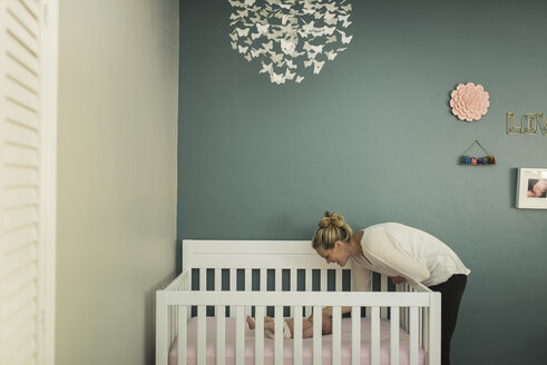 Mother looking at newborn daughter lying in crib against wall - CAVF26987