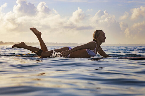 Side view of woman lying on surfboard in sea against cloudy sky - CAVF27107