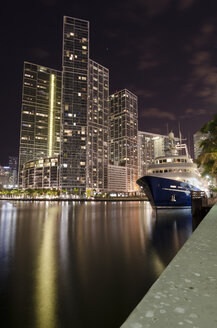 USA, Florida, Miami, High-rise buildings and luxury yacht at night - STCF00557