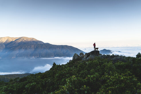 Distant view of woman with dog standing on top of mountain by cloudscape - CAVF27289