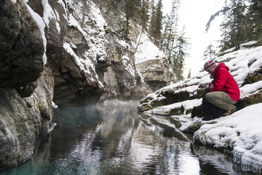 Side view of hiker with backpack crouching by stream at forest during winter - CAVF27343