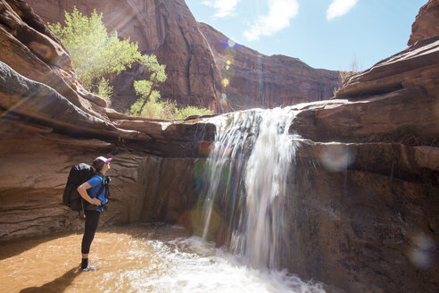 Side view of woman with backpack looking at waterfall against rock formations during sunny day - CAVF27385