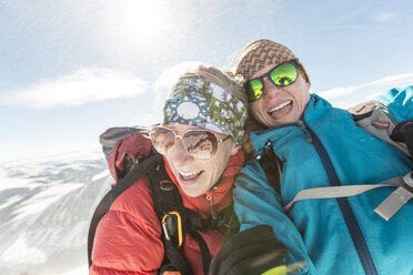 Happy female friends wearing sunglasses and warm clothing against sky - CAVF27394