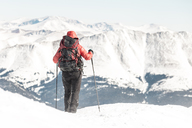 Rear view of female hiker with backpack holding hiking poles while standing against snowcapped mountains - CAVF27397