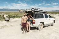 High angle portrait of couple wearing swimwear while standing against off-road vehicle during sunny day at Spencer Hot Springs - CAVF27403