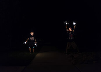 Boys playing with sparklers at night - CAVF27499