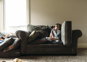 Boy relaxing on sofa at home - CAVF27508