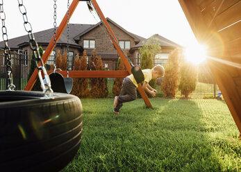 Boy playing on swing at yard - CAVF27517