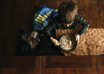 Overhead view of boy eating corn flakes at home - CAVF27520