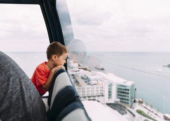 Boy looking through window while sitting in Gondola - CAVF27523
