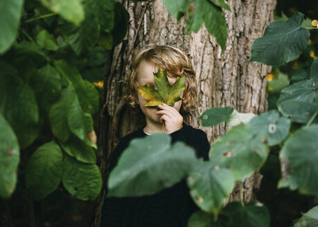 Boy hiding face with leaf while standing against tree - CAVF27538