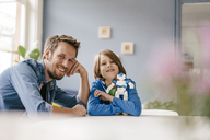 Portrait of happy father and son with robot at home - KNSF03582