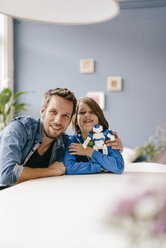 Portrait of happy father and son with robot at home - KNSF03585