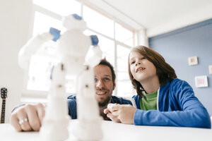 Father and son looking at robot on table at home - KNSF03588